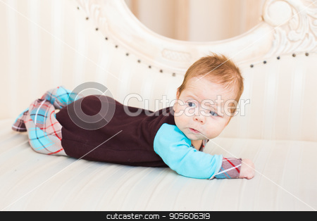 Portrait of a cute newborn baby lying on its stomach and smiling stock photo, A portrait of a cute newborn baby lying on its stomach and smiling by Satura86