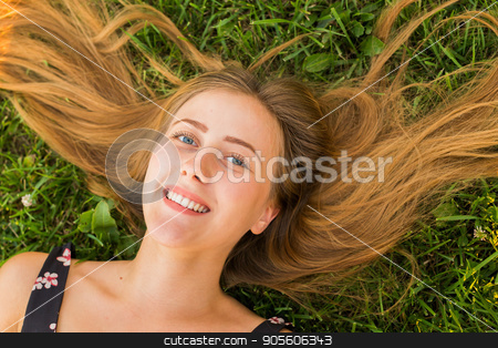 Portrait of a young woman lying on the grass stock photo, Portrait of a young woman lying on the grass by Satura86
