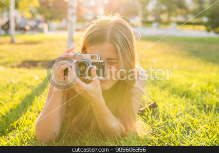 Beautiful girl photographer holds a camera and lying on the grass in the spring outdoors in the park. The concept of tourism and travel stock photo, Beautiful girl-photographer holds a camera and lying on the grass in the spring outdoors in the park. The concept of tourism and travel by Satura86