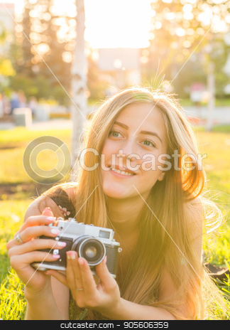 woman the photographer with old camera lays on a grass stock photo, woman the photographer with old camera lays on a grass by Satura86