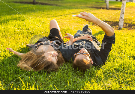 Spring outdoor portrait of young happy couple lying on the grass stock photo, Spring outdoor portrait of young happy couple by Satura86