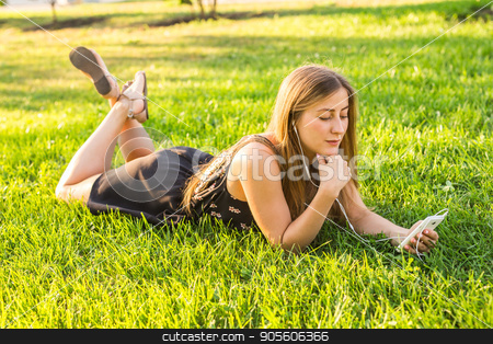 Girl listening to music streaming with headphones in summer on a meadow stock photo, Girl listening to music streaming with headphones in summer on a meadow by Satura86