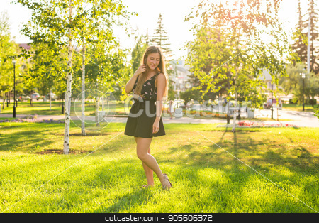 Attractive young woman enjoying her time outside in park with sunset in background stock photo, Attractive young woman enjoying her time outside in park with sunset in background by Satura86