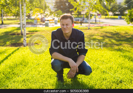 Young funny guy in the park stock photo, Young man in the park listen to the music by Satura86
