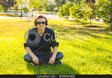 Young man in the park listen to the music stock photo, Young man in the park listen to the music by Satura86