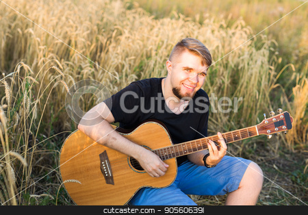 A man is playing guitar in grass field at relax day with sun light stock photo, A man is playing guitar in grass field at relax day with sun light by Satura86