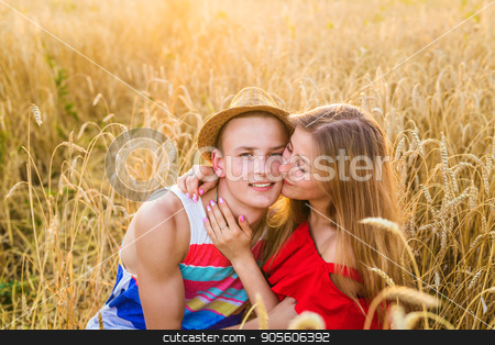 Young love couple kissing on field stock photo, Young love couple kissing on field outdoors by Satura86