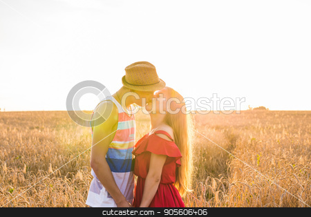 Young love couple kissing on field in sunlight stock photo, Young love couple kissing on field outdoors by Satura86