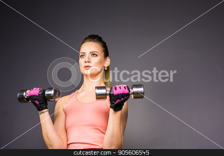 Athletic woman doing exercises with dumbbells in the gym stock photo, Athletic woman doing exercises with dumbbells in the gym by Satura86