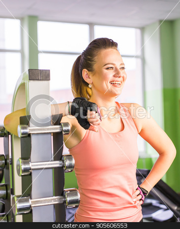 Young adult fit sporty girl posing near shelf with metal dumbbell in gym room space stock photo, Young adult fit sporty girl posing near shelf with metal dumbbell in gym room space by Satura86