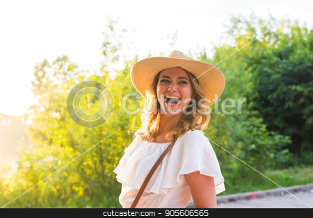 Smiling summer woman with hat stock photo, Smiling summer woman with hat. Laughing young woman enjoying her time outside in park with sunset in background by Satura86