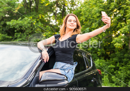 Smiling young woman taking selfie picture with smart phone camera outdoors in car stock photo, Smiling young woman taking selfie picture with smart phone camera outdoors in car by Satura86