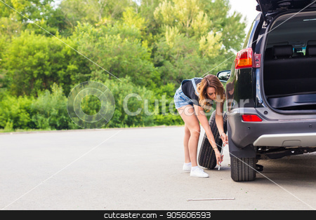 Woman changes the wheel of car on a road stock photo, Woman changes the wheel of car on a road by Satura86
