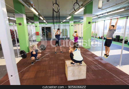 group of people exercising in gym stock photo, fitness, sport and exercising concept - group of people training with different equipment in gym by Syda Productions