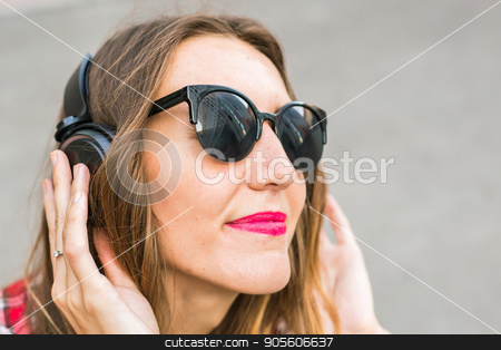 Young smiling woman relaxing and listening to music with headphones in the street stock photo, Young smiling woman relaxing and listening to music with headphones in the street by Satura86