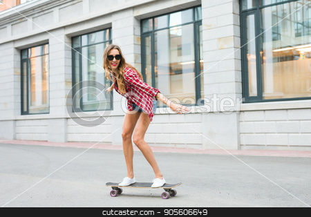 Young woman riding on her skateboard. Female skater practicing skating on the city stock photo, Young woman riding on her skateboard. Female skater practicing skating on the city by Satura86
