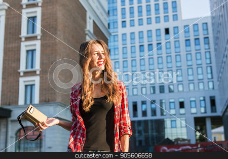 Beautiful young woman with long hair holds in hand virtual reality headset in an urban context stock photo, Beautiful young woman with long hair holds in hand virtual reality headset in an urban context by Satura86