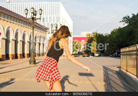 summer holidays, extreme sport and people concept - happy girl riding skateboard on city street stock photo, summer holidays, extreme sport and people concept - happy girl riding skateboard on city street by Satura86