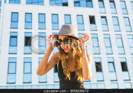 Sunny lifestyle close-up fashion portrait of young stylish hipster woman walking on the street, wearing trendy outfit and hat stock photo, Sunny lifestyle fashion portrait of young stylish hipster woman walking on the street, wearing trendy outfit and hat by Satura86