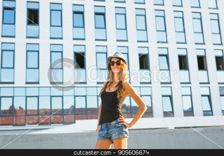 Sunny lifestyle fashion portrait of young stylish hipster woman walking on the street, wearing trendy outfit and hat stock photo, Sunny lifestyle fashion portrait of young stylish hipster woman walking on the street, wearing trendy outfit and hat by Satura86