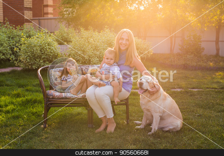 Mother and her daughter and son in the garden with a golden retriever dog stock photo, Mother and her daughter and son in the garden with a golden retriever dog by Satura86