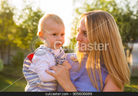 Playful woman in the garden playing with her baby son stock photo, Playful woman in park playing with her laughing son by Satura86