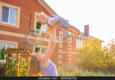 happy harmonious family outdoors. mother throws baby up, laughing and playing in the summer on the nature stock photo, happy harmonious family outdoors. mother throws baby up, laughing and playing in the summer on the nature by Satura86