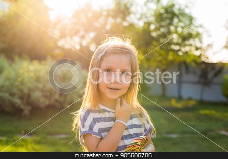 cute little girl eating a lollipop on the grass in summertime stock photo, cute little girl eating a lollipop on the grass in summertime by Satura86