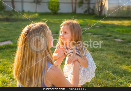 Portrait of happy loving mother and her baby daughter playing outdoors stock photo, Portrait of happy loving mother and her baby outdoors by Satura86