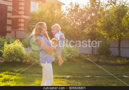happy harmonious family outdoors. mother laughing and playing with baby in the summer on the nature stock photo, happy harmonious family outdoors. mother laughing and playing with baby in the summer on the nature by Satura86