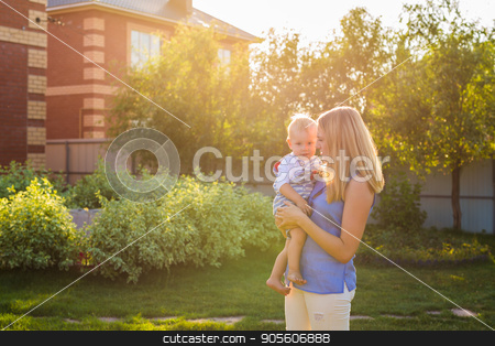 Happy mother holding a young son in the park stock photo, Happy mother holding a young son in the park by Satura86