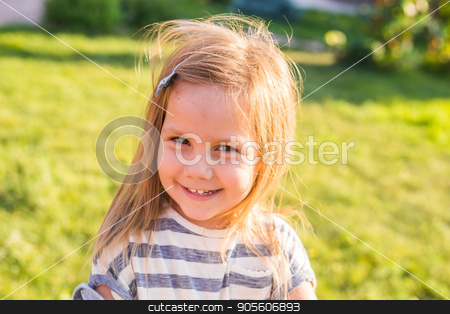 Portrait of sweet little girl play outdoors stock photo, Sweet little girl outdoors with curly hair in the wind by Satura86