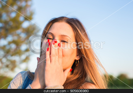 Surprised young woman covering her mouth with hands outdoors stock photo, Surprised young woman covering her mouth with hands outdoors by Satura86