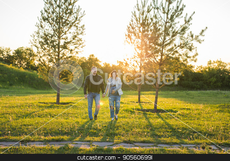 Pregnant woman with husband walking on meadow in the sunlight stock photo, Pregnant woman with husband walking on meadow by Satura86