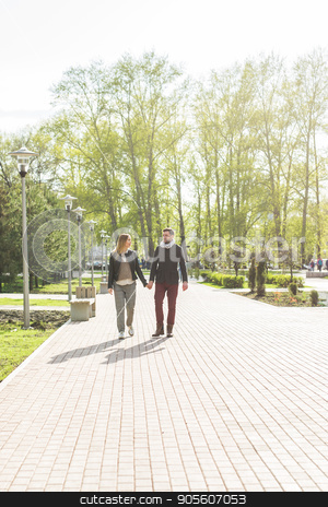 Stylish pregnancy concept - portrait of couple of hipsters husband and wife in trendy clothes walking in the city park stock photo, Stylish pregnancy concept - portrait of couple of hipsters husband and wife in trendy clothes walking in the city park by Satura86