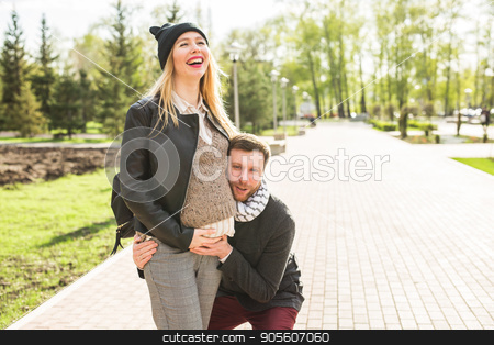 Stylish pregnancy concept - portrait of couple of hipsters husband and wife in trendy clothes walking in the city park