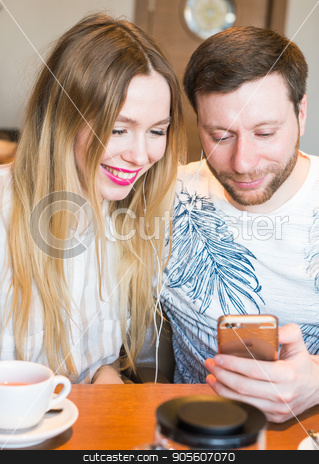 Closeup of couple listening to music with mobile phone at coffee bar. Man and woman listening music with headphones stock photo, Closeup of couple listening to music with mobile phone at coffee bar. Man and woman listening music with headphones by Satura86