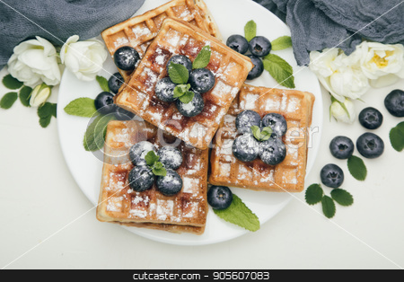 Belgian waffles with blueberries for breakfast stock photo, Belgian waffles with fresh blueberries and mint with white flowers on white table. Delicious dessert. Top view by sunapple
