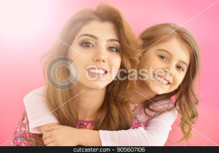 young mother with little daughter stock photo, portrait of beautiful young mother with little daughter on pink background by Ruslan Huzau