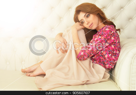 beautiful young woman on white couch stock photo, Portrait of beautiful brunette young woman on white couch by Ruslan Huzau