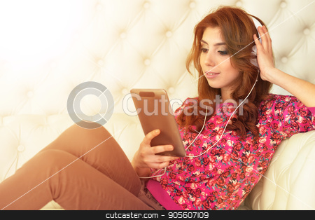beautiful young woman on white couch stock photo, Portrait of beautiful brunette young woman using tablet on white couch by Ruslan Huzau