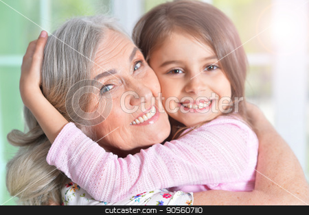 little girl hugging grandmother stock photo, Portrait of a pretty little girl hugging her grandmother by Ruslan Huzau