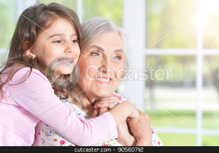 little girl hugging grandmother stock photo, Portrait of a pretty little girl hugging her grandmother by Ruslan Huzau