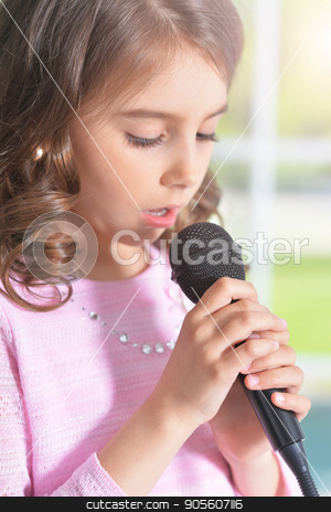 little girl singing with microphone stock photo, close up view of cute little girl singing with microphone by Ruslan Huzau