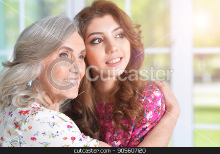 woman hugging daughter stock photo, Portrait of a senior woman hugging her daughter by Ruslan Huzau