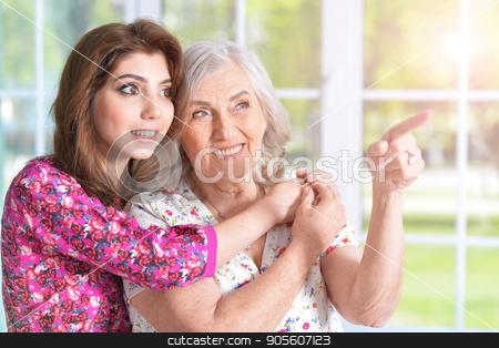 Young woman hugging mother stock photo, Portrait of a young beautiful woman hugging her mother by Ruslan Huzau