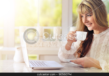 Young woman using laptop  stock photo, Young woman sitting at table and using laptop while drinking tea by Ruslan Huzau
