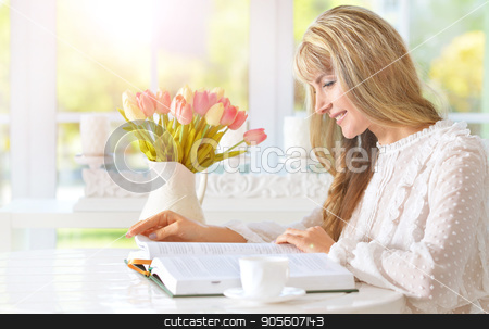 young woman reading book stock photo, Beautiful young woman reading book on light cozy kitchen by Ruslan Huzau