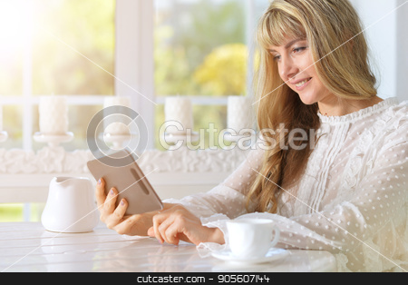 Young woman using digital tablet stock photo, Young woman sitting at table and using digital tablet by Ruslan Huzau
