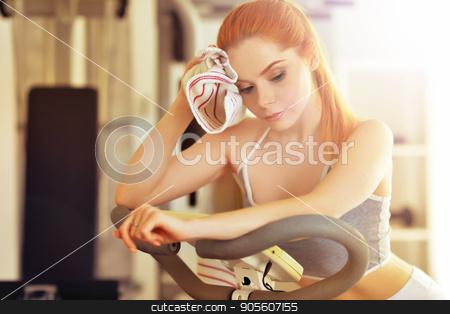 Yung woman training in gym stock photo, Portrait of a sporty young woman training in gym by Ruslan Huzau